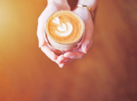 Close up hands of barista woman holding cup of hot cappuccino coffee in the cafe, copy space