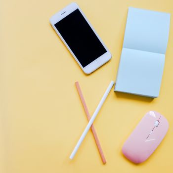 Creative flat lay style workspace desk with smartphone, stationery, mouse and blank note on colorful background with copy space