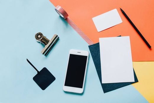 Creative flat lay style workspace desk with smartphone, blank envelope, sunglasses and masking tape on modern colorful background