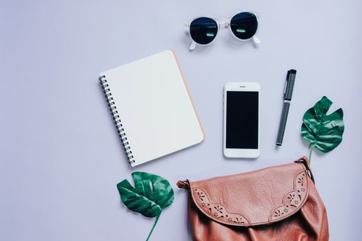 Top view flat lay of woman bag with smartphone, blank notebook, sunglasses and green leaf, copy space