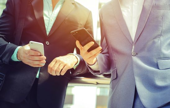 Midsection of two colleague businessmen using smartphone at the outside of modern office building, business and technology concept