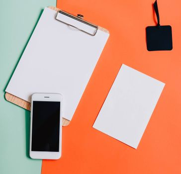 Creative flat lay of smartphone, blank clipboard and white card on minimal color background