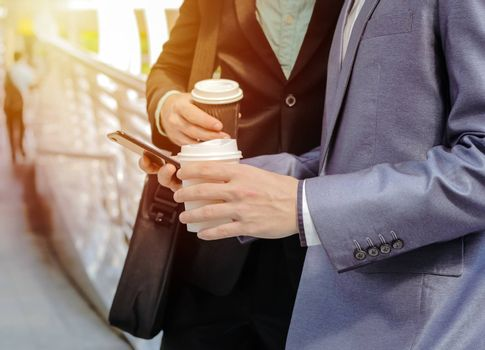 Midsection of two colleague businessmen using smartphone and drinking coffee at the outside of modern office building, business and technology concept