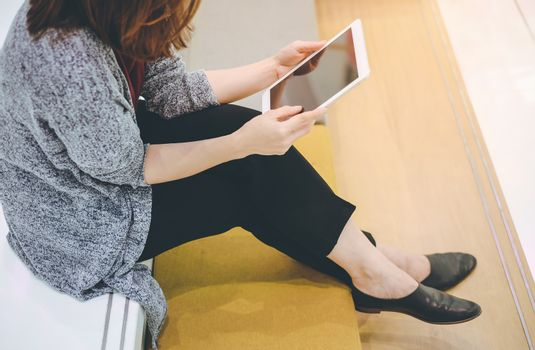 Young asian woman enjoy using tablet in modern office or shopping mall