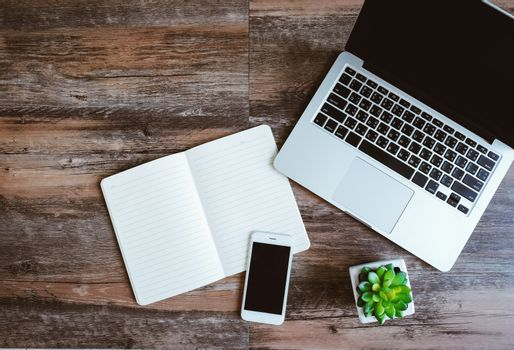 Flat lay photo of workspace desk with laptop, smartphone, blank notebook and green plant with copy space wooden background