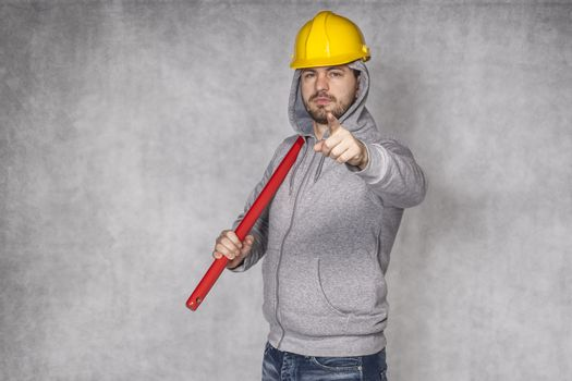 builder on grey background, pointing at you