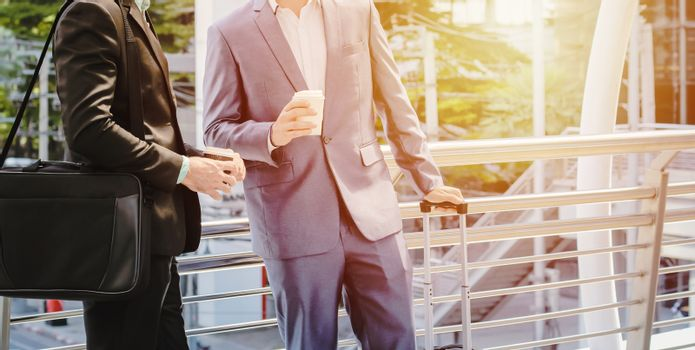 Businesspeople drinking a cup of coffee and holding luggage for business trip at sidewalk of the modern building with sunlight