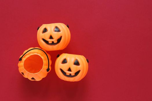 Flat lay style of halloween party concept with decorative plastic pumpkins on red background, copy space