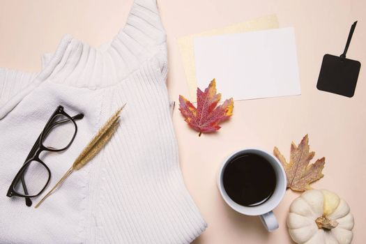 Flat lay of autumn fashion style, sweater, eyeglasses, coffee and blank card with maple leaves, top view