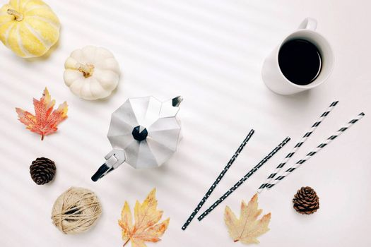 Flat lay of autumn or thanksgiving style concept with coffee, autumn leaves, pumpkins, moka pot and straw
