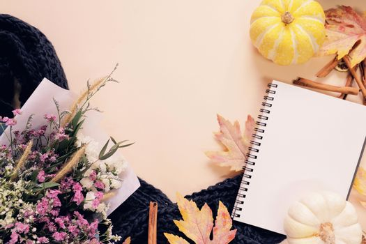 Flat lay style of autumn and thanksgiving with pumpkin, notebook, scarf, bouquet of flower and maple leaf, copy space