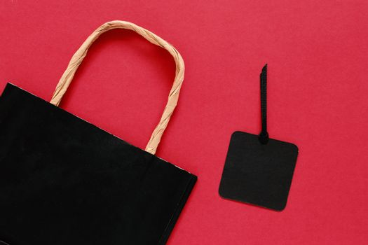 Mock up pf shopping bag with blank sale tag on red background, copy space,  shopping concept