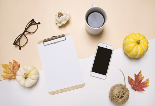 Creative flat lay of workspace desk in autumn style with blank clipboard, smartphone, eyeglasses, pumpkins, coffee and autumn leaves with copy space background, minimal style