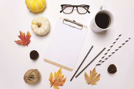 Flat lay of autumn or thanksgiving style concept with coffee, autumn leaves, pumpkins, coffee and clipboard on white background