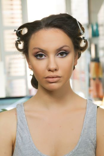 The girl poses with makeup and curlers
