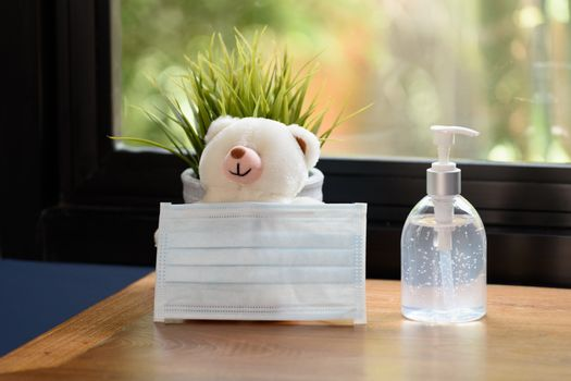 Hand sanitizer,surgical mask,teddy bear and flower pot on wood table with green nature background while Covid-19  home quarantine .
