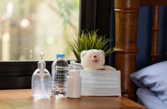 Hand sanitizer,surgical mask,teddy bear and medicine on wood table with green nature background while Covid-19  home quarantine .