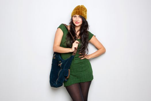 unique young woman standing with hat and purse