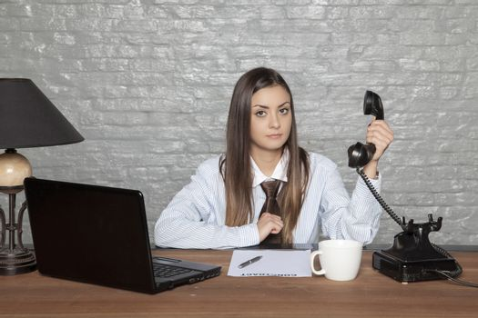 disgusted by a conversation, a business woman is holding a handset from a distance