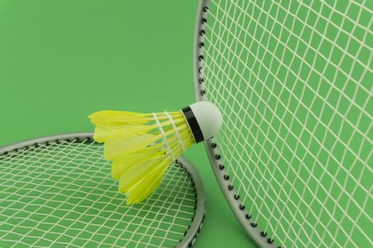 Badminton rackets and yellow feathered shuttlecock