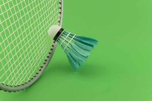 Badminton rackets and blue feathered shuttlecock