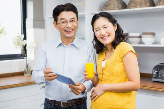 Happy expectant couple using tablet