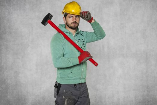 happy worker with a hammer on his shoulder and a helmet on his head