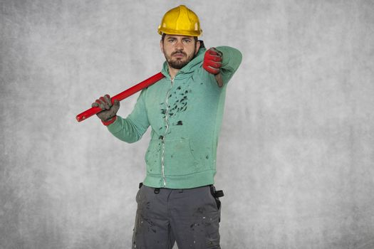 Worker shows thumbs down, hammer on shoulder