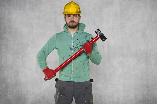 A well-built worker holds a great hammer