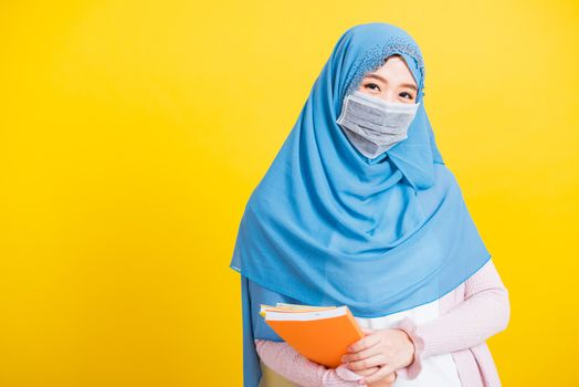 Asian Muslim Arab, Portrait of young woman religious wear veil hijab and face mask protective to prevent coronavirus she student hold books on hand, isolated on yellow background, Back to college