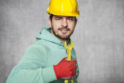 smiling worker holding a yellow key in a hand
