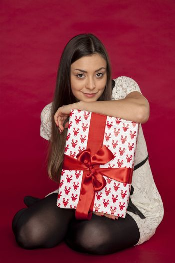 The thoughtful girl leaning against the gift, red background