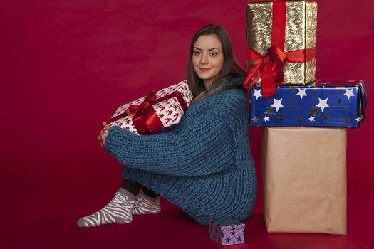 The young girl in a blue sweater is sitting next to gifts