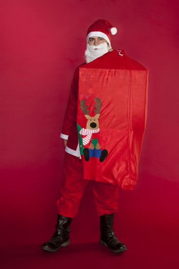 Santa Claus holds a heavy bag on his back