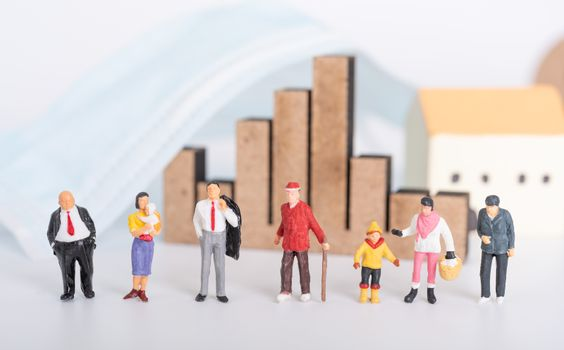Miniature people family with surgical mask,business graph and house icon on white background due to Coronavirus disease (COVID-19) prevention,people or economy