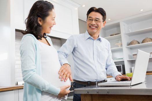Happy expectant couple using laptop
