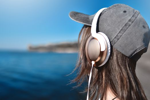 Happy joyful woman listening to music while being outdoor. Music concept.