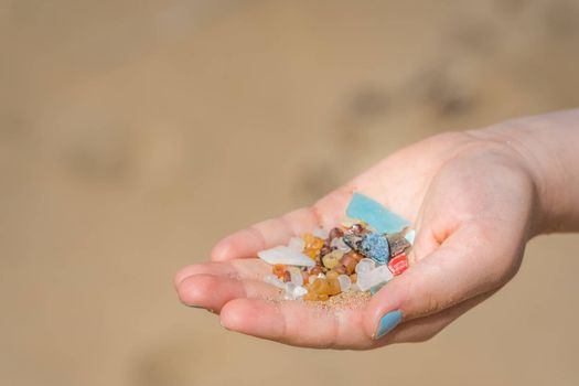 Little girl holding small tiny harmful plastic microbeads collected on the beach in Zante, Zakynthos, Greece