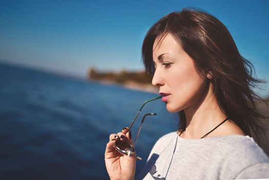 Fine art portrait of a beautiful adult woman on the sea river on the pier