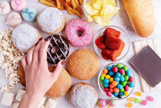 Fast food concept. Unhealthy food. Unhealthy food and fast food with donuts, chocolate, burgers and sweets top view