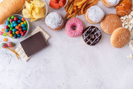 Fast food concept. Unhealthy food. Unhealthy food and fast food with donuts, chocolate, burgers and sweets top view with copy space