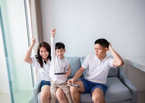 Asian family having fun playing computer console games together, Father and son have the handset controllers and the mother is cheering the players at home