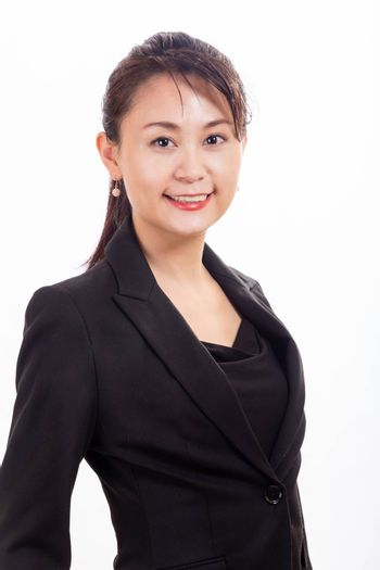 Asian American businesswoman looking at camera on white background