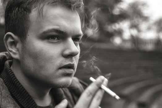 Guy smokes a cigarette outside, portrait, close-up