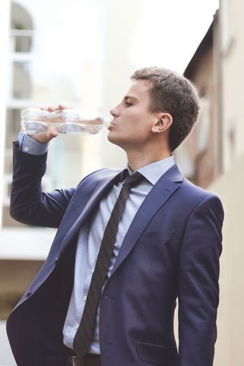 Business man with suit holding water bottle and drinking outdoor. The young Business man drink fresh water