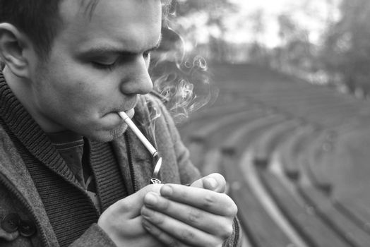 Guy smokes a cigarette outside, portrait, close-up