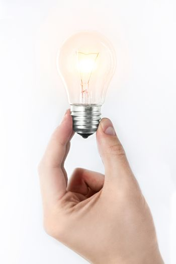 A man's hand holding a burning light bulb on a white background