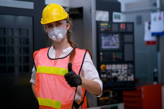 Factory woman worker or technician with mask stand with confident action in front of machine and show thumbs up.