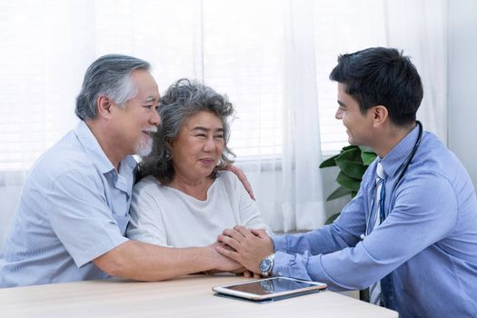 The doctor with blue shirt and stethoscope encourage old man by holding their hands and woman about their health during a visit home for check-up elder people at home for elderly good healthcare.