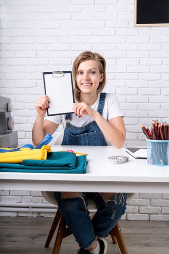 Young blond woman tailor showing a sketch ready to sew a pillow